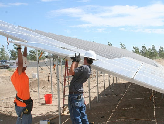 Workers install a solar panel at Silver Stage High