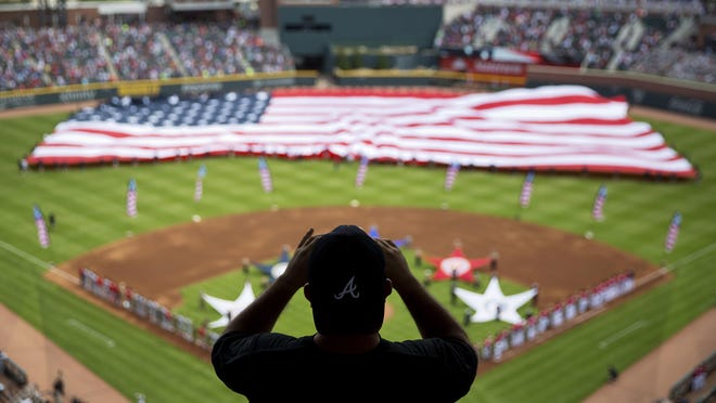 FILE - In this May 20, 2017, file photo, a spectator takes a photo of a United States flag as it is unveiled for the national anthem as part of Military Appreciation Day before a baseball game between the Atlanta Braves and the Washington Nationals in Atlanta. The anthem has been a standard part of U.S. sports games since World War II. Experts say Game 1 of the 1918 World Series between the Boston Red Sox and the Chicago Cubs helped pave the way. The song became the official national anthem in 1931. (AP Photo/David Goldman, File)