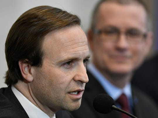 Michigan Lt. Governor Brian Calley, front, addresses the audience as Dr. Jim Hines listens during a gubernatorial town hall meeting, Monday, Feb. 12, 2018 at the Troy Community Center.