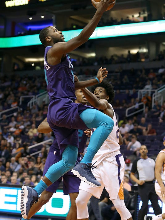 CORRECTS TO SUNDAY NOT SATURDAY - Charlotte Hornets guard Michael Kidd-Gilchrist, left, drives to the basket past Phoenix Suns' Josh Jackson during the first half of an NBA basketball game Sunday, Feb. 4, 2018, in Phoenix. (AP Photo/Ralph Freso)