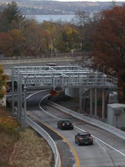 Cars travel under an electronic toll gantry on the