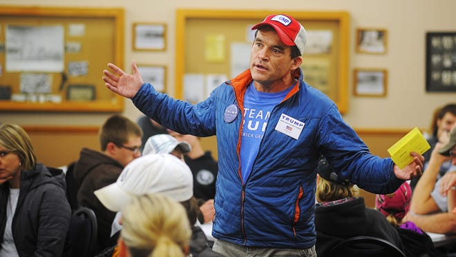 Chris Hupke, with the Donald Trump campaign, speaks to caucusgoers about Donald Trump during the Republican caucus Monday, Feb. 1, 2016, at the Larchwood Community Center in Larchwood, Iowa.