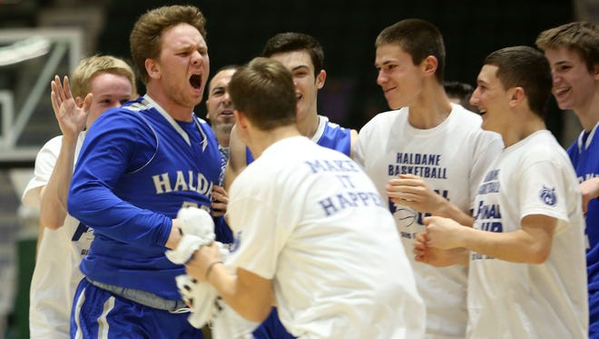 Haldane's Aidan Siegel (25) is mobbed by teammates after hitting a big 3-point basket  against Moravia during the boys Class C semifinal at the Glens Falls Civic Center March 11, 2016. Haldane won the game 36-34.