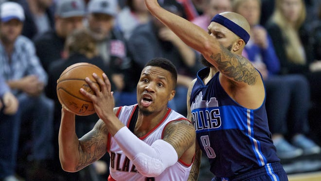 Portland Trail Blazers guard Damian Lillard, left, drives past Dallas Mavericks guard Deron Williams, right, during the second half of an NBA basketball game in Portland, Ore., Wednesday, March 23, 2016.