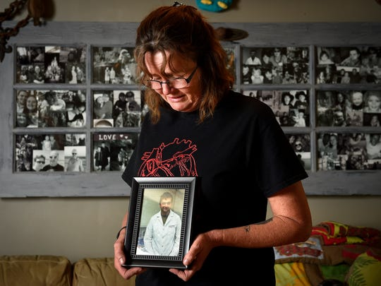 Carol Akers, mother of Jacob Akers, holds a photo of