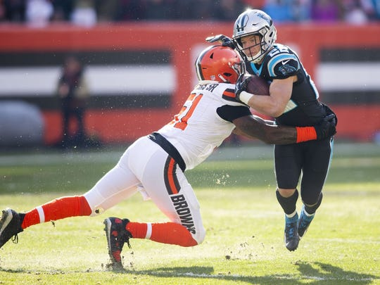 Dec 9, 2018; Cleveland, OH, USA; Carolina Panthers running back Christian McCaffrey (22) runs through a hit by Cleveland Browns outside linebacker Jamie Collins (51) during the first quarter at FirstEnergy Stadium. Mandatory Credit: Scott R. Galvin-USA TODAY Sports