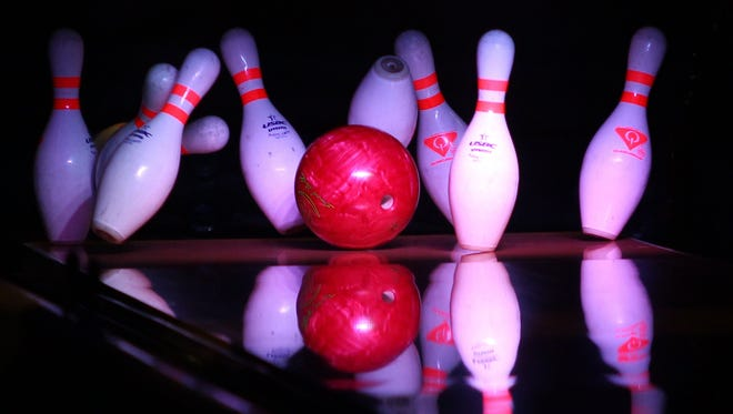A bowling ball knocks over pins at Head Pinz in Fort Myers, Florida, on Monday, July 20, 2015.