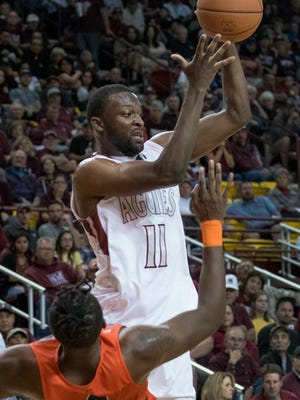 NMSU forward Johnathan Wilkins tries to get rid of the ball but makes contact with UTEP's Tirus Smith and gets called for the charging foul Saturday night at the Pan American Center.