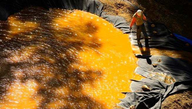 A man pours a combination used to take the sediments out of the water and reduce acidity of one of the retention ponds at the bottom of Gold King Mine on August 13, 2015 at Gladstone townsite. Members of the EPA, Environmental Restoration, Weston Solutions and the U.S. Coast Guard are working on cleaning up the water in the four retention ponds and helping with the creation of the fifth.