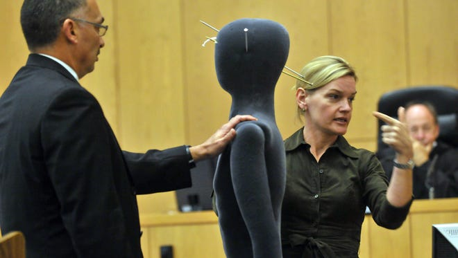 Oct. 2010: Asst. State Attorney John Molchan, left, holds onto a mannequin while Medical Examiner Andi Minyard, illustrates the path of the bullet wounds to Byrd Billings during her testimony against Leonard Patrick Gonzalez, Jr. Gonzalez is on trial for the home invasion and murders of Byrd and Melanie Billings.