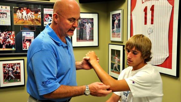 Dr. Tim Kremchek examines a student-athletes' arm.