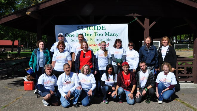 A group of walkers in the 2014 Out of the Darkness walk in Wausau pose for a photo.