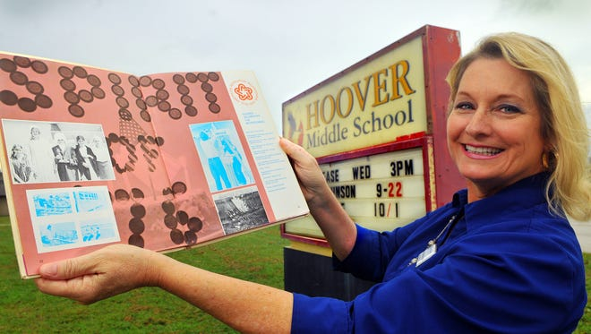 Dawn Atkinson Spaccio shows her class of 1976 yearbook with a photo of students packing the missing time capsule.