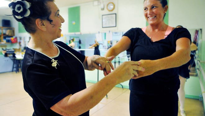 Dance Instructor Liz Bevilacqua of Merritt Island works with Florida Today fitness reporter Michelle Mulak trys  as she trys her hand at ballet Monday evening in the Teen/Adult Ballet class held at  Dussich Dance Studio on Merritt Island under the direction of Liz Bevilacqua of Merritt Island  .