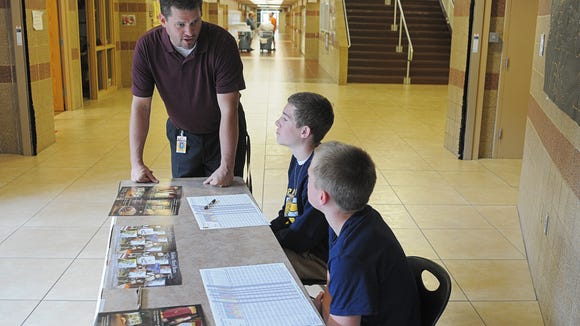 Ryan Rollinger, Harrisburg High School assistant principal, talks with Ryan Meyer, center, and Max Johnson, right, both 14 and Harrisburg High School freshman, as the sell fruit for an FFA fundraiser during parent-teacher conferences Thursday, Oct. 8, 2015, at Harrisburg High School in Harrisburg, S.D. Rollinger tackled Mason Buhl, a student and shooting suspect, after principal Kevin Lein was shot in the arm in his office.