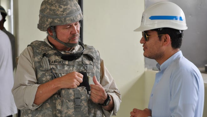 Left, Clark Carroll, USACE-TAA, project engineer for the Marshal Fahim National Defense University projects, talks with a Local National Quality Assurance representative after a walk-through inspection of one of building under construction at MFNDU. LNQAs play a vital role, working as USACE's eyes and ears on the ground at project sites that are not always accessible to U.S. personnel.