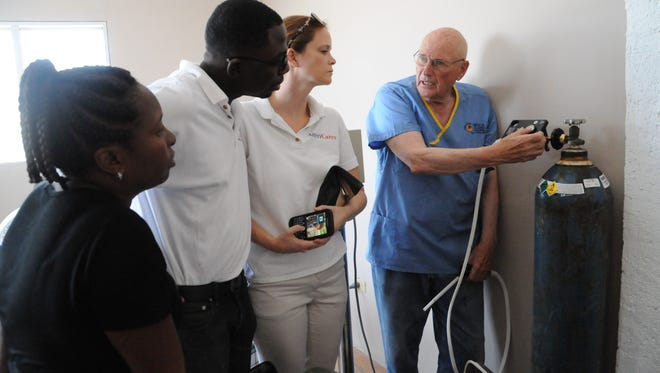 Dr. Robert Hilgers, right, shows directors from AmeriCares  how screening and treatment work in the clinic in Gonaives, Haiti.