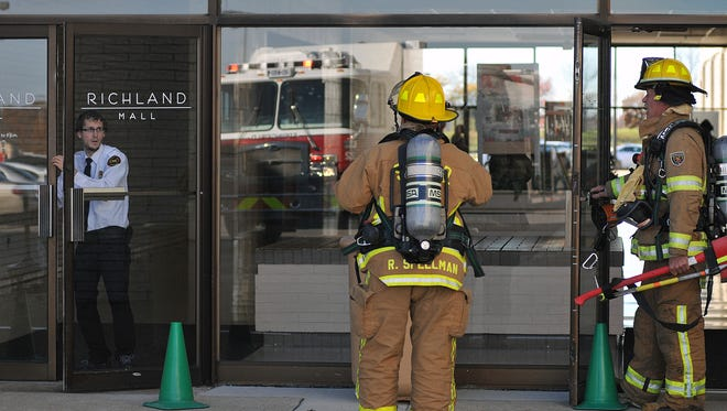 A security guard locks the doors at the Richland Mall as firefighters enter to investigate a suspicious smell.