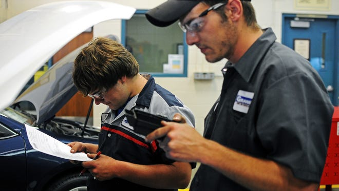 Jordan Tunge looks over a worksheet while working with Sam Roberts, both second year automotive technology students at Southeast Technical Institute, during an automotive electronics lab on Friday, Sept. 19, 2014, at Southeast Technical Institute in Sioux Falls, S.D.