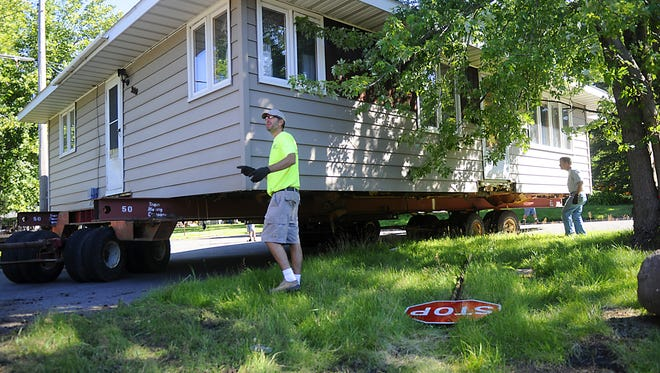Laborers moved a house along Benton County Road 3 in Sauk Rapids earlier this year to make way for the reconstruction project.