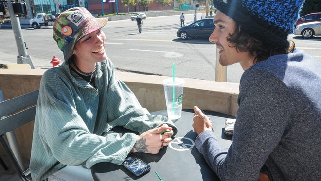 Cintamani Schwab, left, and Chris Jordan, both 23, chat Monday over a beverage at the Starbucks outdoor patio on East University Avenue.