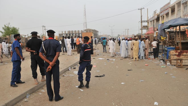 Security officers stand guard at the scene of an explosion at a mobile phone market in Kano, Nigeria, on Nov. 18, 2015. Wednesday Nov. 18, 2015.