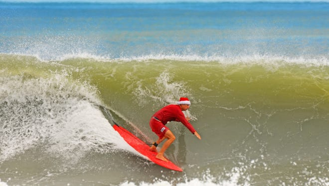 Hunter Joslin, dressed in holiday garb, tucks into a nice wave in Cocoa Beach.