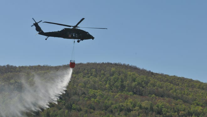 In this May 8, 2013, file photo, a helicopter helps douse fires sparked by the use of munitions and small arms during the weekend training of the Vermont Army National Guard at the Ethan Allen Firing Range in Jericho, Tuesday.