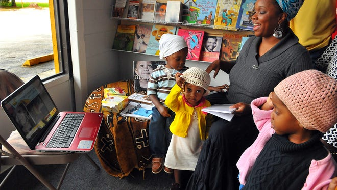 Emunah Y'srael of Palm Bay reads 50 Year's in Chains by Charles Ball during Thursday's live web cast held at Essence of Knowledge Urban Book Store in Cocoa as her children  M'ale age 4, Tucolyah 22 months and M'layah age 4 look on.