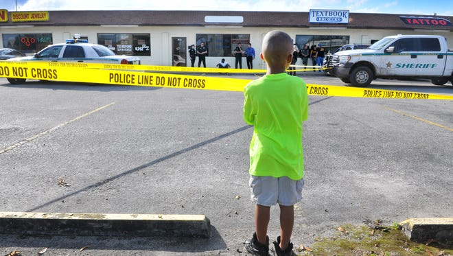 FILE- A child looks on as Brevard County Sheriff Agents, Deputies and also the Sheriff Task Force investigate the scene where two men were shot on Clearlake road in Cocoa.
