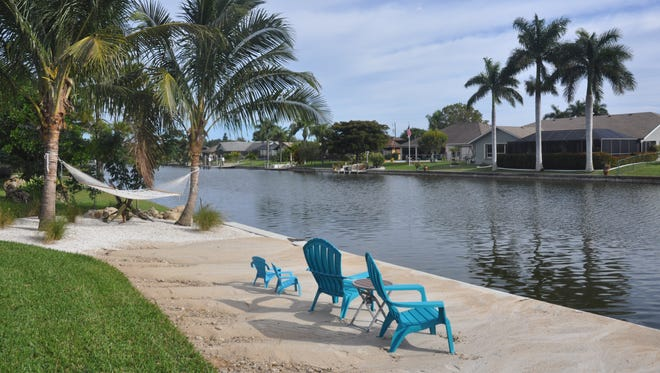 Bright blue Adirondack chairs and hammocks provide place to relax on this beach behind a home in Cape Coral built by Sposen Signature Homes.