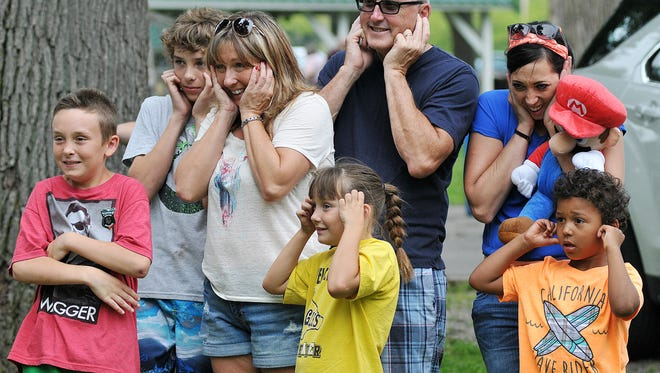 Spectators cover their ears as a cannon goes off during the Red, White and Blues in the Park Festival last July at Aumiller Park.