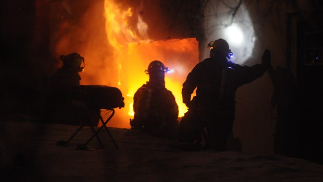 Firefighters work as flames pour from a house in Sauk Rapids on Saturday night.