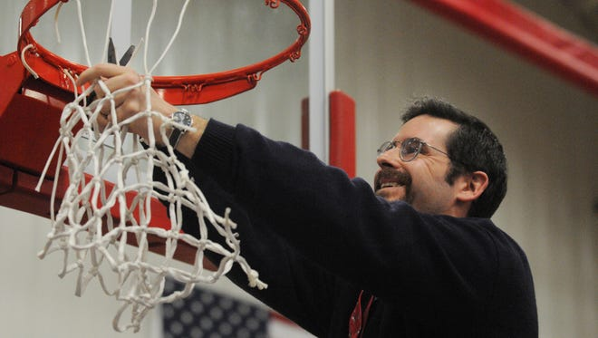 Worcester Prep head coach Keith Geiger cuts down the net after winning the ESIAC Tournament title against Delmarva Christian on Friday in Berlin.