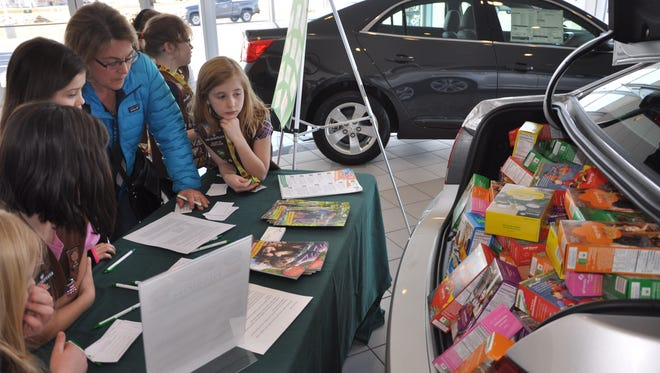 Members of Brownie Troop 80067 look on as a woman tries to guess how many Girl Scout cookies are packed into the trunk of a Chevrolet Cruze at Jennings Chevrolet Buick GMC on Saturday, Feb. 27.