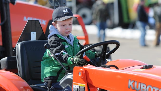 Sam Lenz tries out the driver's seat of this Kubota  tractor at the WPS Farm show on the EAA grounds in this file photo. This year's Farm Show runs through Thursday, March 31.