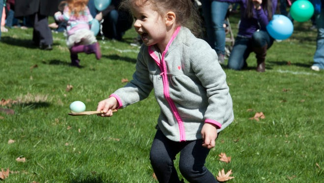 Theia Tucker, 3, of Fremont, smiles while carrying an egg. Hundreds of children participated in the annual Easter Egg Roll at the Rutherford B. Hayes Home and Museum in  Fremont on Saturday.