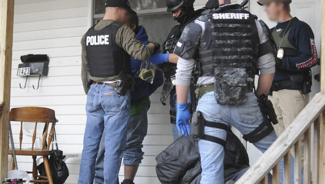 Members of the Drug Task Force look through the personal items of a person of interest who was on the porch of a house the unit raided on Sixth Street in Port Huron in October 2012. MARK R. RUMMEL/ TIMES HERALD.