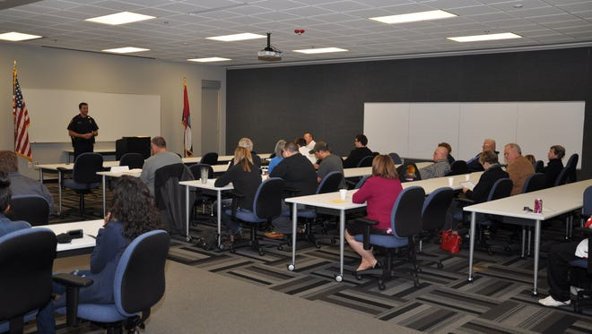People at the Citizen's Police Academy listen to an officer.