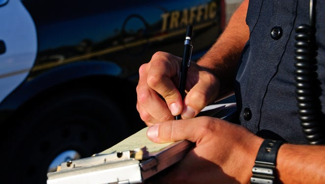 A police officer writes a ticket.