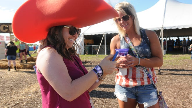 Emma Rickelman of Madison wears her big hat as she chats with Jordan Bork of Wisconsin Dells, at  Country USA 2015 in Oshkosh. This year's event runs through Saturday.