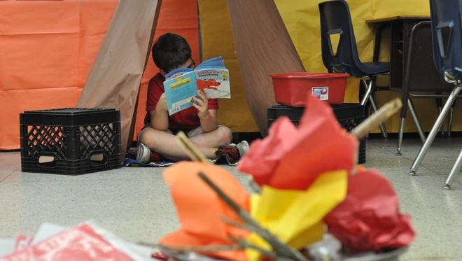 A third-grader reads by a campfire in a tent at Pineville Elementary School during Rapides Literacy Camp.