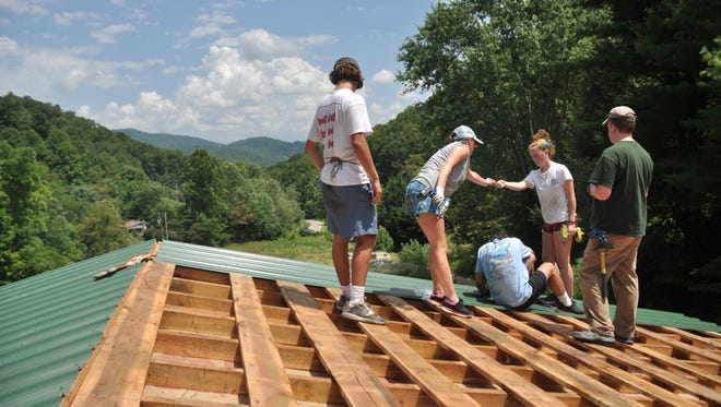 Volunteers from Holy Trinity Episcopal in Greensboro install a new metal roof on a home in the Grapevine community.