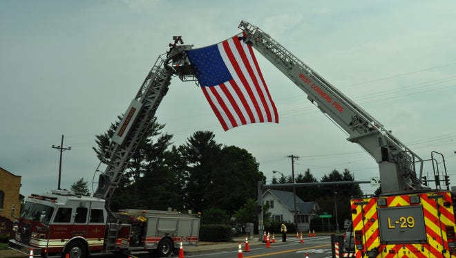 Fire vehicles hold the American flag outside Our Lady of Good Counsel Church in Endicott for Tioga County Fire Coordinator John Scott's funeral.