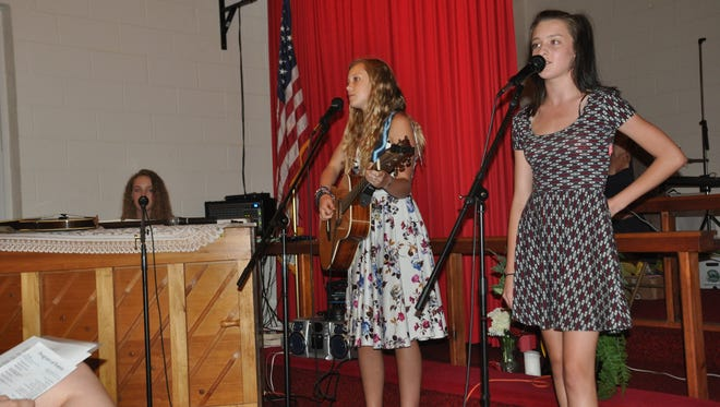 PAGE students Scarlet Ramsay, Gretchen Hauser and Angelena Avery perform at the ceremony celebrating the program's seventh year in Madison County.