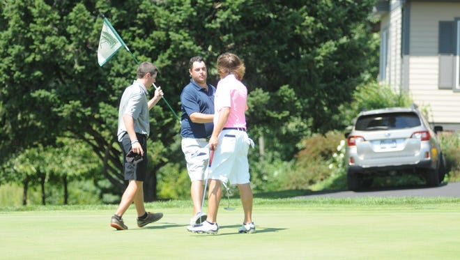 Brian Viola shakes Ian Wilson's hand as Erik Stauderman carries the flag. The three were grouped together in the first round of the Dutchess County Amateur Friday.