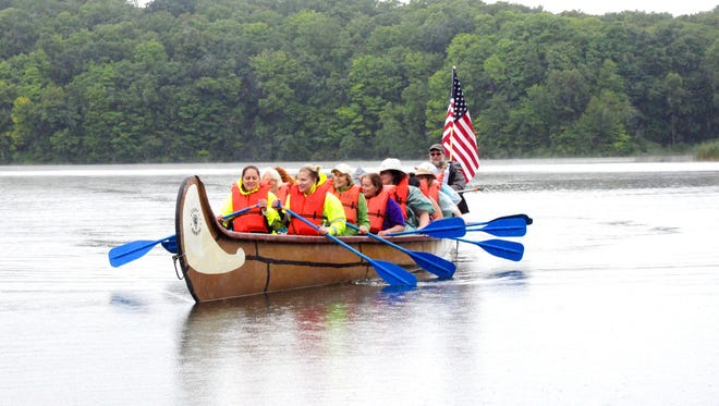 Participants in the 19th annual Women in the Outdoors weekend paddle a voyageur canoe on Little Elkhart Lake near Plymouth, Wisconsin.