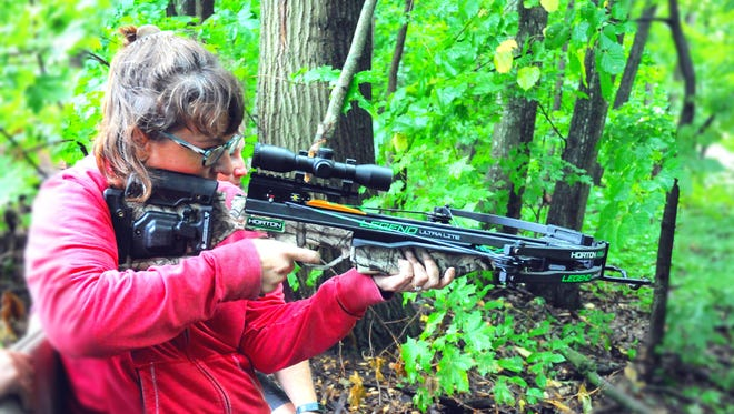 A participant prepares to shoot a crossbow at the 19th annual Women in the Outdoors weekend.