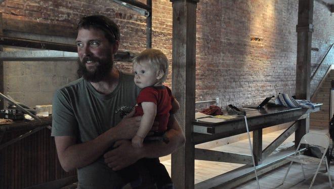 Brandon Edwards holds his son Audie as he prepares to open Madison County Brewing Company.