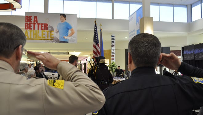 Lincoln County Sheriff Dennis Johnson and Sioux Falls Police Chief Matt Burns stand at attention for the retiring of the flags at Project Blue Light ceremony Thursday, Oct. 13, 2016.